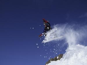 Male Snowboarder Flying Through the Air