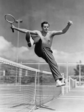 Male Tennis Player Jumping over Net