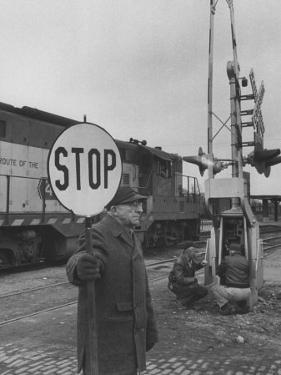 Man Holding Stop Sign by Hand While Automatic Gate Is Being Repaired