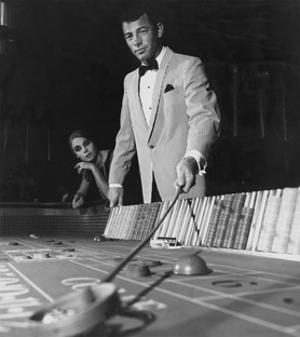 Man in One-Button Pinstripe Jacket Works a Table at a Casino by 0 0