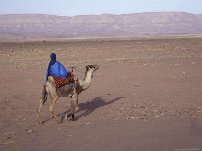 https://imgc.allpostersimages.com/img/posters/man-in-traditional-dress-riding-camel-morocco_u-L-P5871W0.jpg?p=0