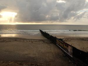 Man Jogs by the Beach Towards the Wall Dividing Mexico and the U.S. in Tijuana, Mexico