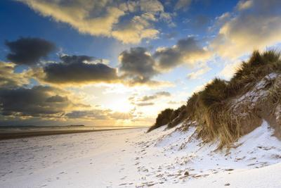 https://imgc.allpostersimages.com/img/posters/man-walks-dog-on-snow-covered-bamburgh-beach-at-dawn-with-view-to-farne-islands_u-L-PQ8S4B0.jpg?p=0