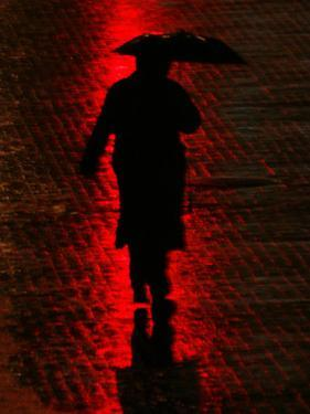 Man Walks Through the Rain in the Financial District in New York