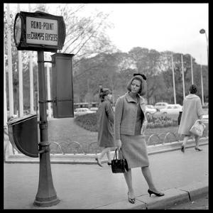 Claudia Cardinale Waiting Near the Champs-Elysées Roundabout, April 1964 by Marcel Begoin
