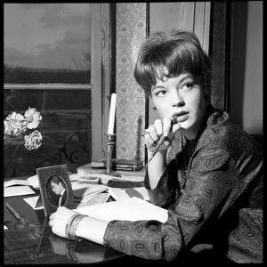 Romy Schneider, Thougthful, Trying to Write a Letter in Front of Alain Delon's Picture by Marcel Begoin