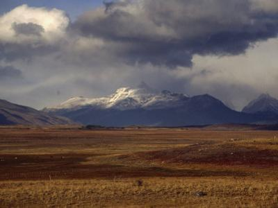 Scenic View of Snow-Capped Mountains, Clouds, and Grasslands