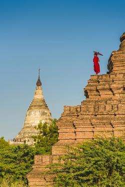 Bagan, Mandalay region, Myanmar (Burma). A young monk watching the Shwesandaw pagoda. by Marco Bottigelli