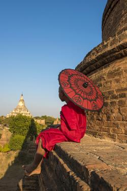 Bagan, Mandalay region, Myanmar (Burma). A young monk with red umbrella watching the Shwesandaw pag by Marco Bottigelli