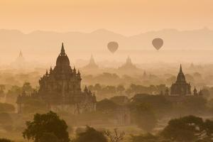 Bagan, Mandalay region, Myanmar (Burma). Pagodas and temples with balloons at sunrise. by Marco Bottigelli