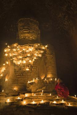 Bagan, Mandalay region, Myanmar (Burma). Young monk praying at a giant brick-make statue of the Bud by Marco Bottigelli