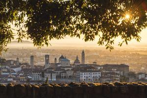 Bergamo, Lombardy, Italy. High angle view over Upper Town (Città Alta) at sunrise. by Marco Bottigelli