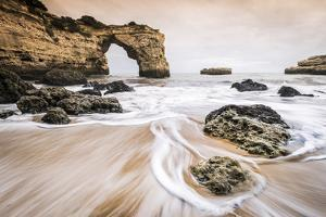 Praia de Albandeira, Lagoa, Algarve, Portugal. Waves between the rocks on the beach. by Marco Bottigelli