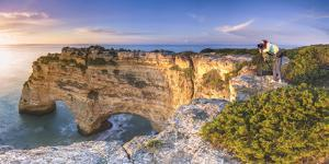 Praia de Marinha, Caramujeira, Lagoa, Algarve, Portugal. Panoramic view of a woman photographing th by Marco Bottigelli