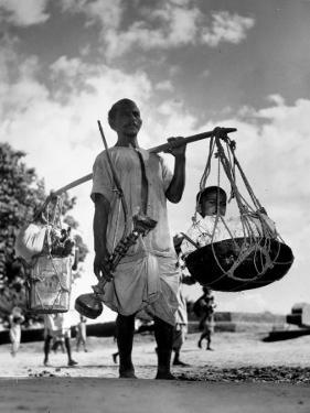 Muslim Man carrying his son and hookah in Convoy to West Punjab to Escape Anti Muslim Sikhs by Margaret Bourke-White
