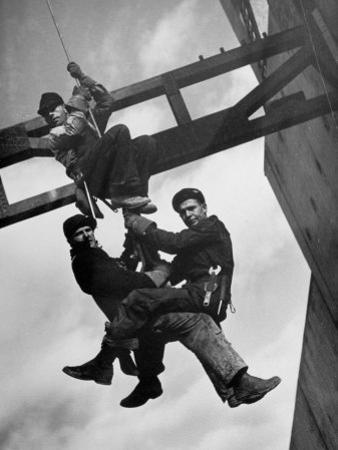 Relief Workers Hanging from Cable in Front of a Giant Beam During the Construction of Fort Peck Dam by Margaret Bourke-White