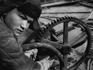 Russian Steel Worker Turning Gear Wheel in a Steel Mill by Margaret Bourke-White