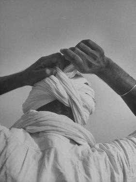 Sikh Man Demonstrating How He Finishes the Winding of His Traditional Turban around His Head by Margaret Bourke-White