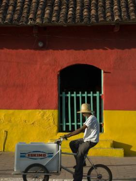 Ice Cream Vendor Riding Bicycle Past Colourful House, Granada, Nicaragua by Margie Politzer