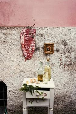 Raw Pork Ribs Hanging on the Wall of a House, Next to a A Gold-Framed Picture by Maria Brinkop