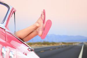 Freedom Car Travel Concept - Woman Relaxing with Feet out of Window in Cool Convertible Vintage Car by Maridav