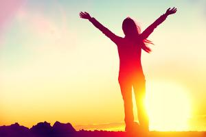 Happy Celebrating Winning Success Woman at Sunset or Sunrise Standing Elated with Arms Raised up Ab by Maridav