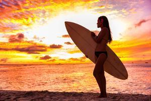 Surfer Bikini Girl on Hawaii Beach Holding Surf Board Watching Ocean Waves at Sunset. Silhouette Of by Maridav