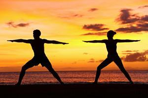 Yoga People Training and Meditating in Warrior Pose Outside by Beach at Sunrise or Sunset by Maridav
