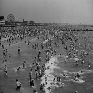 Huge Crowd Gathered in the Surf and at the Beach in Front of Coney Island Amusement Park by Marie Hansen