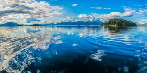 Clouds and sky reflected in the calm waters of the Inside Passage, Southeast Alaska, USA by Mark A Johnson