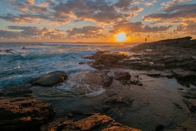 Fisherman fishing off rocks at sunrise, Queensland, Australia by Mark A Johnson