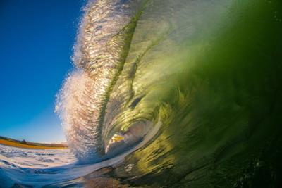 Frilly Lip-A powerful breaking wave backlit at sunrise, Hawaii by Mark A Johnson