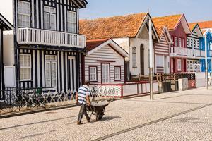 Man in a striped shirt wheeling a wheelbarrow, Bairro dos Pescadores, Aveiro, Portugal by Mark A Johnson