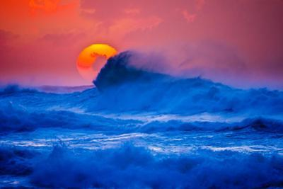The setting sun and large winter waves breaking off the north coast of Kauai, Hawaii by Mark A Johnson
