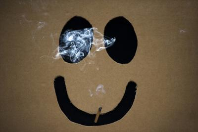 Smoking a Marijuana Joint Inside a Box with a Happy Face Cut Out before the Global Marijuana March