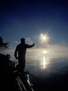 Silhouette of Fisherman Casting a Line into Lake, Ontario, Canada by Mark Carlson