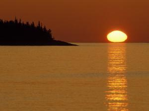 Spring Sunrise Silhouettes Edwards Island and Reflects Light on Lake Superior by Mark Carlson