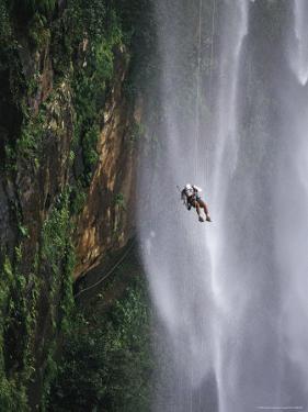 Climber Dangles on Rope Near a Waterfall in Nordeste, Brazil by Mark Cosslett