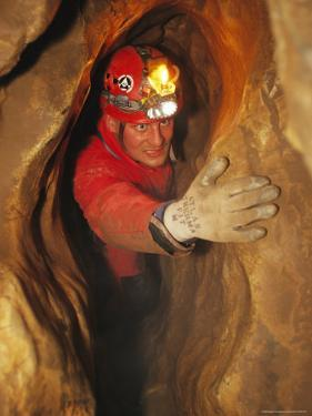 Man in Caving Gear in the Entrance to the Laundry Chute, a Narrow Corridor in the Rats Nest Cave by Mark Cosslett