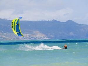 Man Kiteboarding in Turquoise Water Ocean off Maui Island by Mark Cosslett