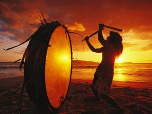 Native Hawaiian Man Beats His Drum on Makena Beach at Sunset by Mark Cosslett
