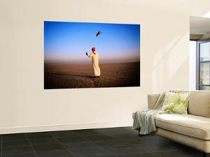 Arab Handler Swinging Lure During Hunting Falcon Training Exercise in Desert by Mark Daffey