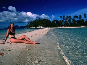 Woman Sunbathing on Sand Spit of Snick Island, El Nido, Philippines by Mark Daffey