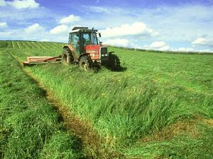 Tractor Cutting Grass Meadow for Silage Farming, UK by Mark Hamblin
