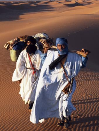 Berber Tribesmen Lead their Camels Through the Sand Dunes of the Erg Chegaga, in the Sahara Region  by Mark Hannaford