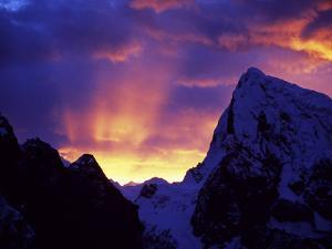 Rays of Sunlight Illuminate the Clouds over the Mountains to the West of Gokyo at Sunrise by Mark Hannaford