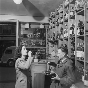 Young Woman Drinking a Bottle of Coca Cola in a Shop, Paris, France, 1950 by Mark Kauffman