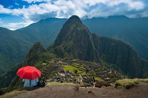 Tourist under the Shade of A Red Umbrella Looking at Machu Picchu by Mark Skalny