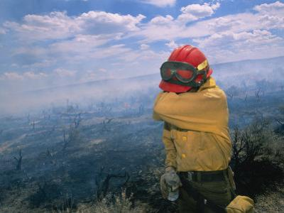 A Fire-Fighter Wipes His Smoke-Irritated Eyes
