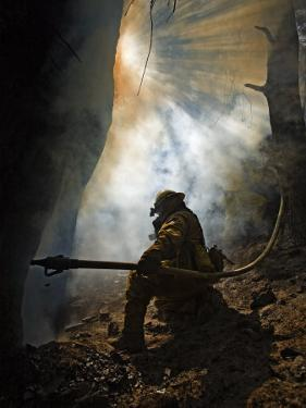 A firefighter blasts water in attempts to drown stubborn flames by Mark Thiessen